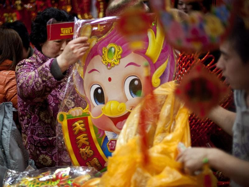 A woman looks at a New Year decoration at a market in Beijing, China. Chinese will celebrate the Lunar New Year on Jan 23 this year. (AP Photo/Andy Wong)