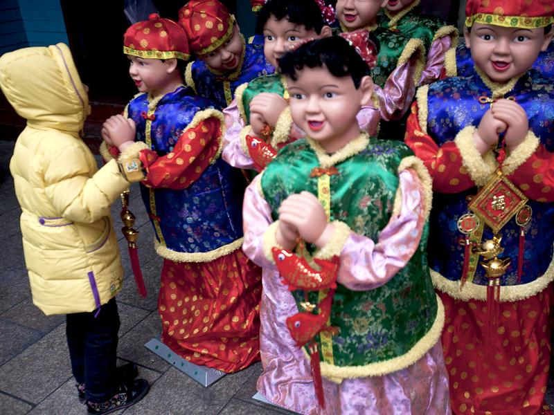 A child looks at mannequins dressed in New Year costumes on display for sale outside a market in Beijing. (AP Photo/Andy Wong)