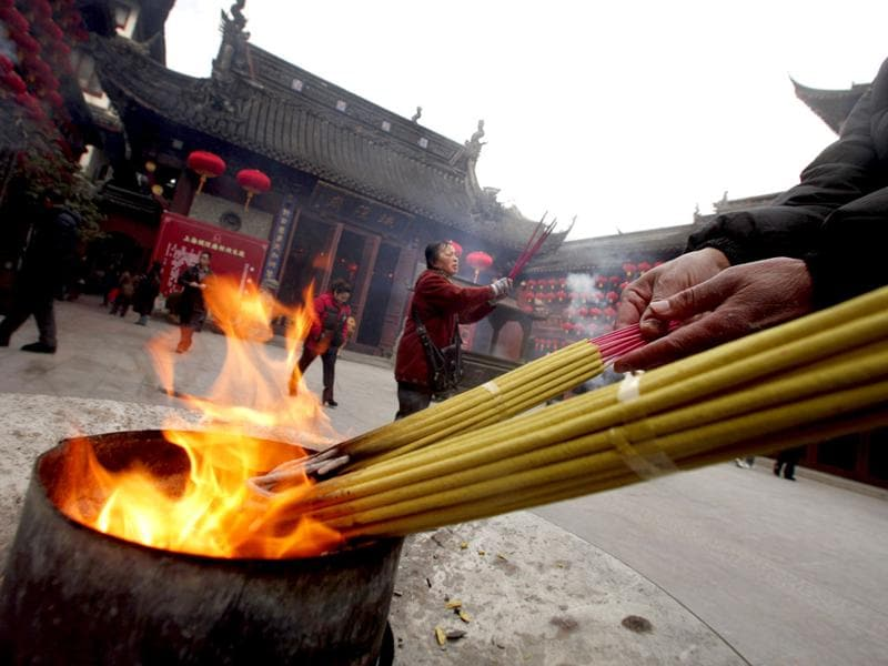 People burn incense sticks as they pray at the Old City God Temple in Yuyuan Garden, downtown Shanghai.