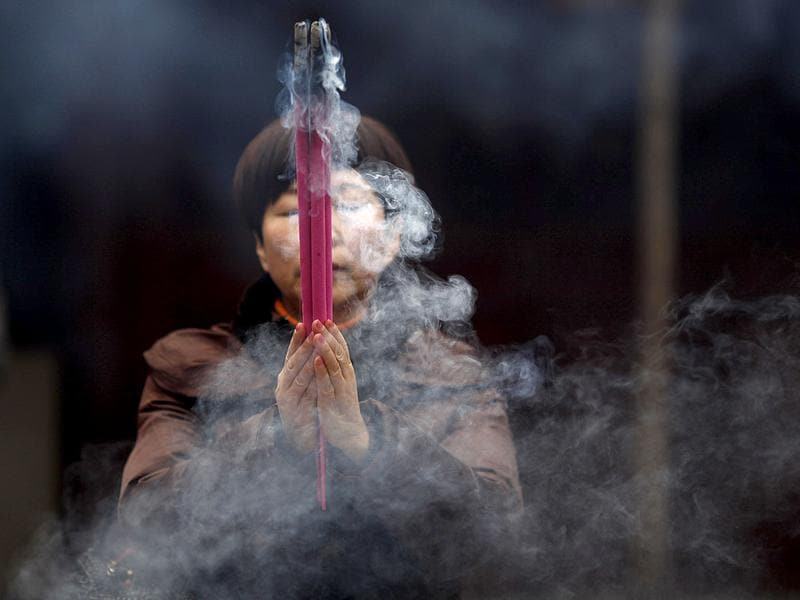 People burn incense sticks as they pray at the Old City God Temple in Yuyuan Garden, downtown Shanghai. Reuters