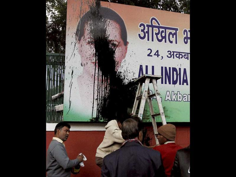 Workers clean a billboard of Congress Party President Sonia Gandhi outside AICC headquarters in New Delhi after Baba Ramdev supporters threw ink on it. PTI Photo