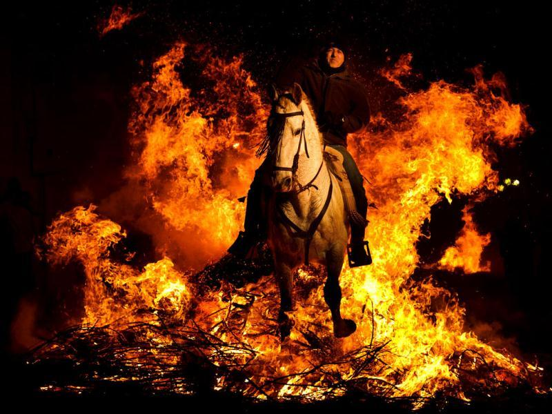 A man rides a horse through a bonfire in San Bartolome de Pinares, Spain, in honor of Saint Anthony, the patron saint of animals. On the eve of Saint Anthony's Day, hundreds ride their horses trough the narrow cobblestone streets of the small village of San Bartolome during the 'Luminarias' a tradition that dates back 500 years and is meant to purify the animals with the smoke of the bonfires and protect them for the year to come. (AP Photo/Daniel Ochoa de Olz)
