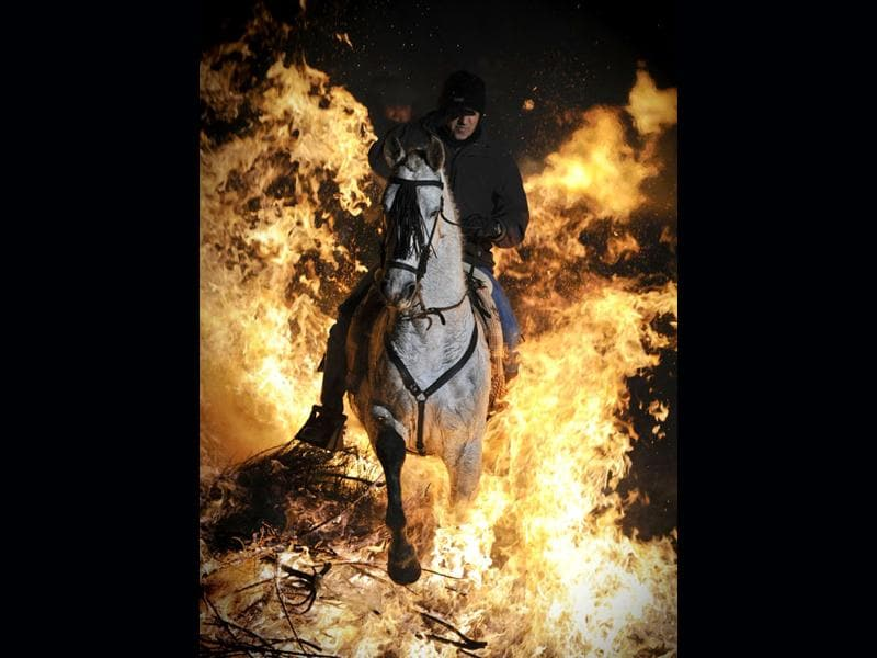 A horseman jumps over a bonfire in the central Spanish village of San Bartolome de Pinares to open the celebrations for the feast of Saint Anthony, patron saint of animals. AFP Photo/Pedro Armestre