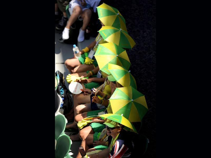 Spectators with umbrella hats watch the women's singles first round match between Sorana Cirstea of Romania and Samantha Stosur of Australia on day two of the 2012 Australian Open tennis tournament in Melbourne. Cirstea upset Stosur 7-6, 6-3. (AFP Photo)