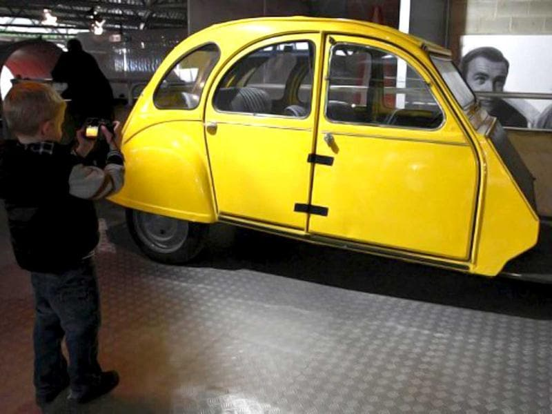 A boy takes a photograph of a Citroen 2CV, which is believed to be the only 1 of 6 remaining from the filming of the 1981 Bond film For Your Eyes Only, on display at the Bond in Motion exhibition at the Beaulieu National Motor Museum in Hampshire. AFP photo