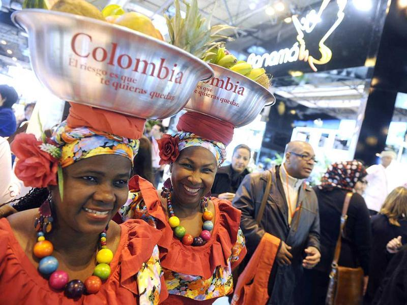 Colombian women carrying tropical fruits are pictured at the Colombian stand during the inauguration of the International Tourism Trade Fair in Madrid. AFP photo
