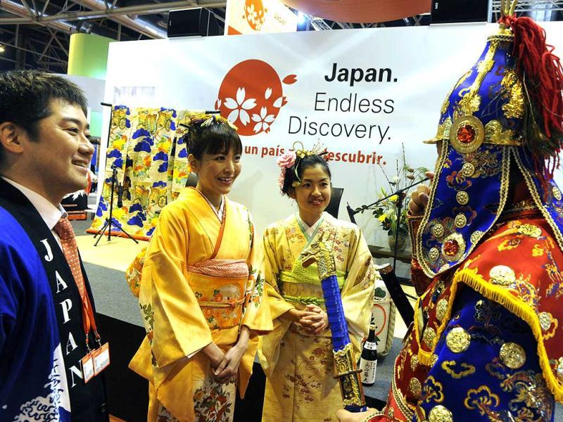 A Korean steward (R) speaks with Japanese hostesses in front of the Japanese stand during the inauguration of the International Tourism Trade Fair. AFP photo