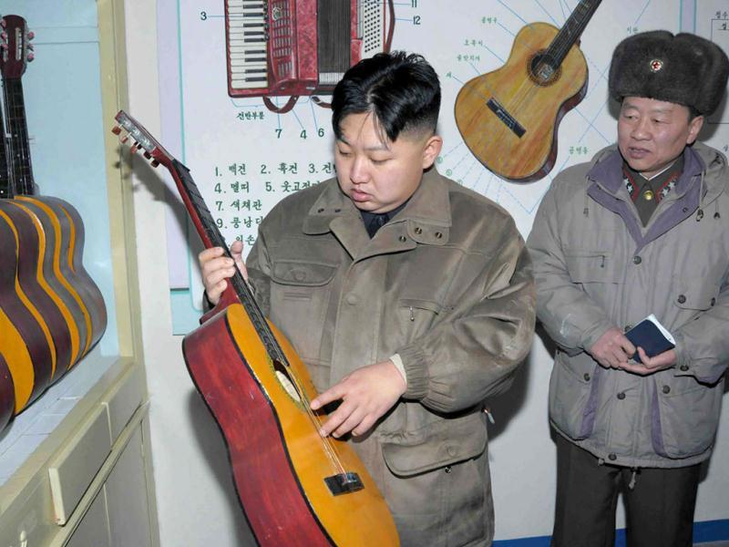 In this undated photo released by the Korean Central News Agency and distributed in Tokyo by the Korea News Service, North Korean leader Kim Jong Un, center, looks at a guitar at an undisclosed location in North Korea. KCNA reported he was inspecting a military unit. AP Photo/Korean Central News Agency via Korea News Service