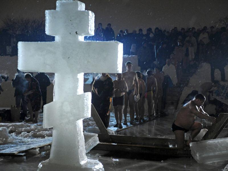 The picture shows Russian Orthodox church faithful gathering around a bath of ice cold water as they take turns plunging into it to mark Epiphany in Moscow's Kolomenskoye open-air museum, former Russian czars' country estate. AFP Photo / Andrey Smirno