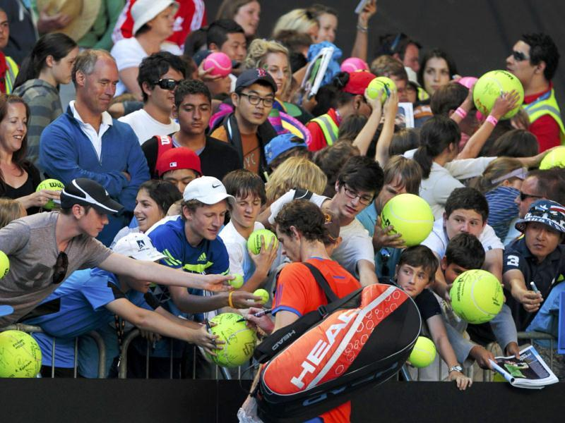 Andy Murray of Britain sign autographs after defeating Edouard Roger-Vasselin of France during their men's singles match at the Australian Open tennis tournament in Melbourne. (Reuters)