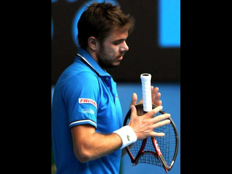 Stanislas Wawrinka of Switzerland holds his broken racquet during his men's singles quarter-final match against Roger Federer of Switzerland on the ninth day of the Australian Open tennis tournament in Melbourne on January 25, 2011. Federer won 6-1. 6-3. 6-3. AFP
