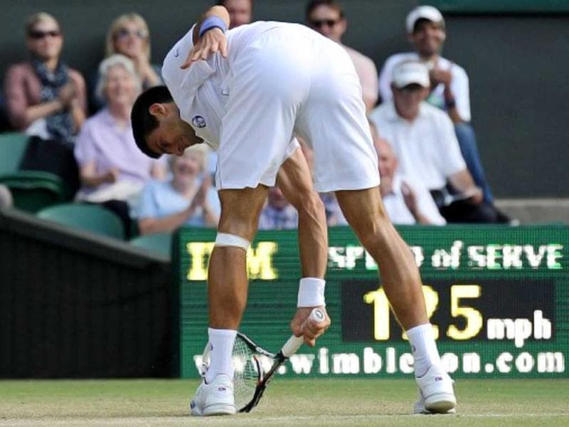 Serbian player Novak Djokovic smashes his racket as he plays against Cypriot player Marcos Baghdatis in a Men's Singles match at the 2011 Wimbledon Tennis Championships at the All England Tennis Club, in south-west London, on June 25, 2011. AFP