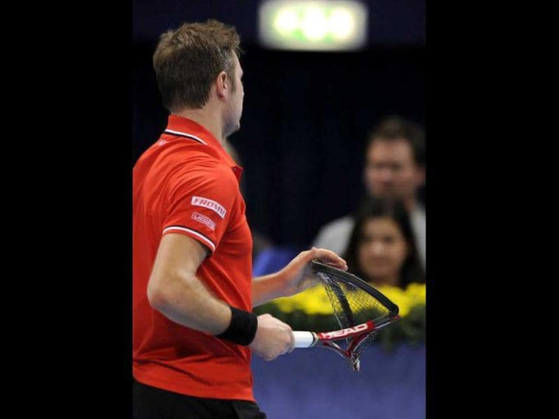 Switzerland's Stanislas Wawrinka walks back to his seat with a racket he broke during his semi-final match against compatriot Roger Federer at the Swiss Indoors ATP tennis tournament on November 5, 2011, in Basel. Federer won 7-6 (7/5), 6-2. AFP