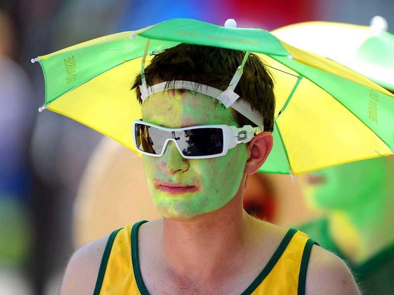 A spectator wears an umbrella hat as he attends the men's singles first round match between Rui Machado of Portugal and David Ferrer of Spain on day two of the 2012 Australian Open tennis tournament in Melbourne. AFP Photo/Nicolas Asfouri