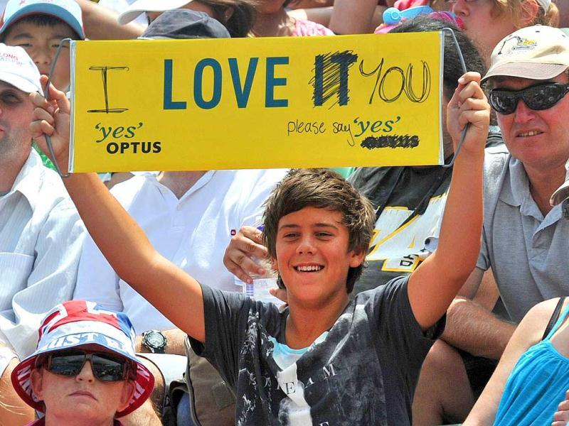 A young tennis fan holds up a sign saying