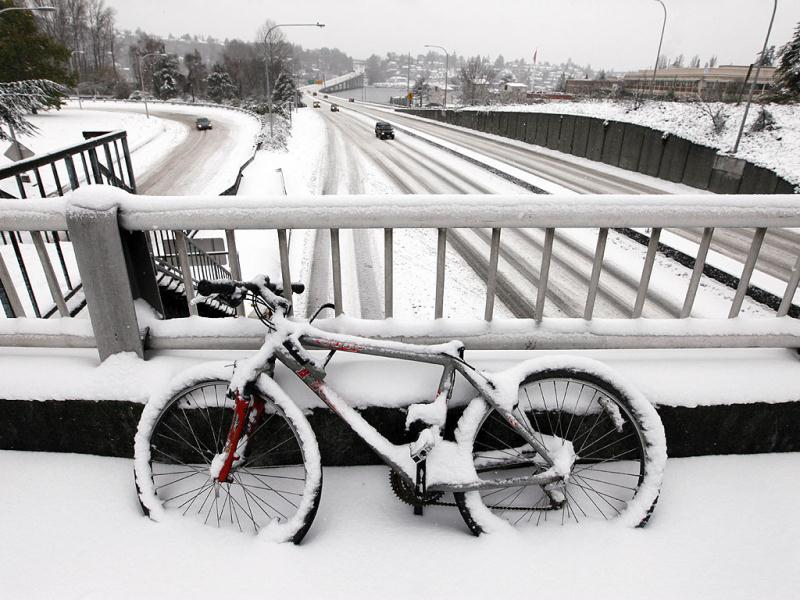 A snow-covered bicycle is locked to a bridge as unusually light traffic drives past below on Highway 520 near the University of Washington in Seattle. A monster Pacific Northwest storm coated the Seattle area in a thick layer of ice Thursday and brought much of the state to a standstill, sending hundreds of cars spinning out of control, temporarily shutting down the airport and knocking down so many trees that members of the Washington State Patrol brought chain saws to work. AP Photo/Elaine Thompson