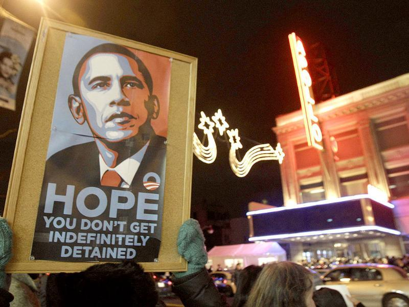 An Occupy Harlem protester holds up a sign protesting the policies of US President Barack Obama across the street from Harlem's famed Apollo Theater where the president held one of several fundraisers he attended in New York. (AP Photo/Kathy Willens)