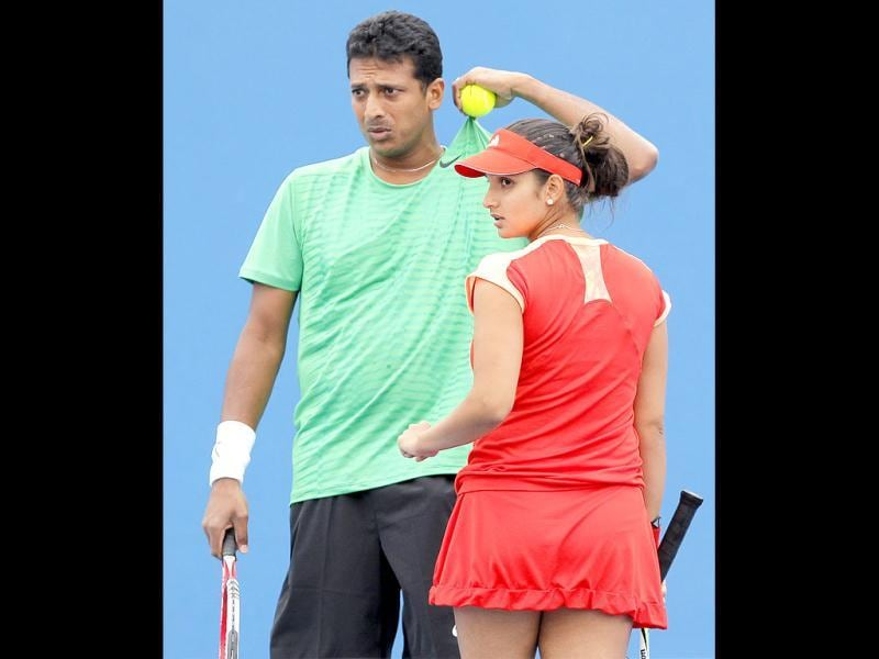 Sania Mirza, right, and Mahesh Bhupathi, left, talk as they play Natalie Grandin of South Africa and Jean-Julien Rojer of Curacao during their mixed doubles first round match at the Australian Open tennis championship, in Melbourne, Australia. (AP Photo)