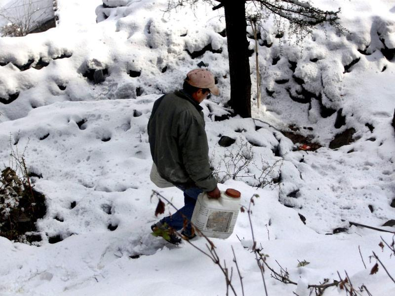 A man walks to fetch water in the snow-covered Bhagsu village in Dharamshala after heavy snowfall in Himachal Pradesh. PTI