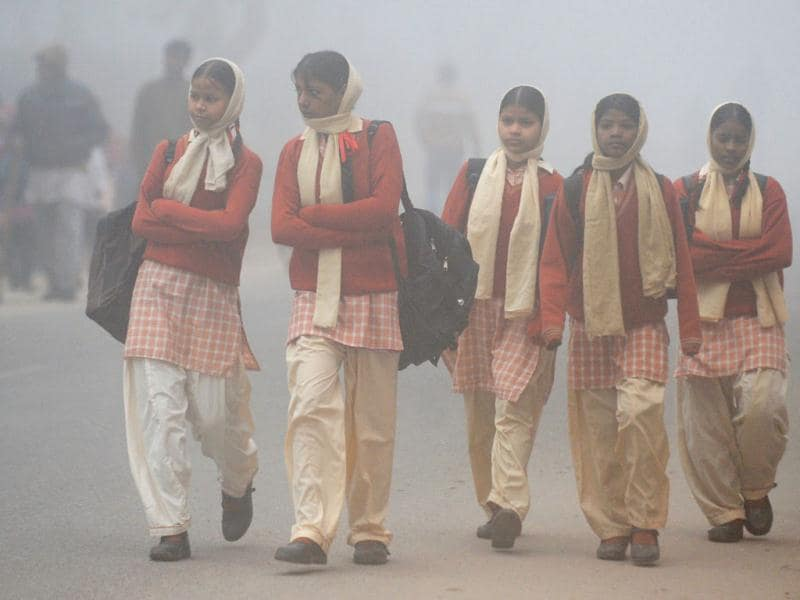 Schoolgirls walk down a road during a foggy and cold morning in New Delhi. AFP/Raveendran
