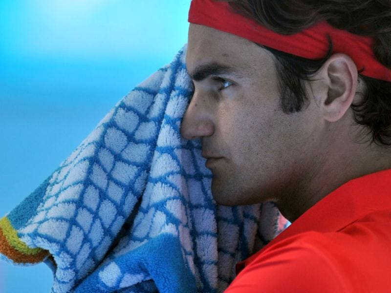 Roger Federer of Switzerland wipes his face during a break against Ivo Karlovic of Croatia in their third round men's singles match on day five of the 2012 Australian Open tennis tournament in Melbourne. Federer won 7-6, 7-5, 6-3. AFP photo / Paul Crock