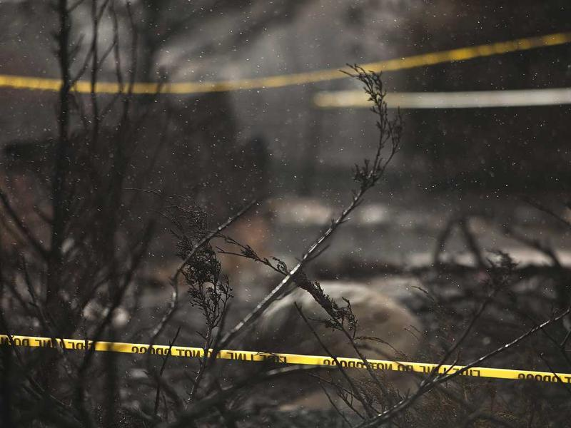 Rain and warning tape blow through the burned brush surrounding the remains of a burned home south of Reno, Nevada. A fierce brush fire on the outskirts of Reno, Nevada, left 26 houses in ruins, but most of the thousands of people chased from their homes were allowed to return even as a major freeway remained closed on Friday, officials said. Reuters/Max Whittaker