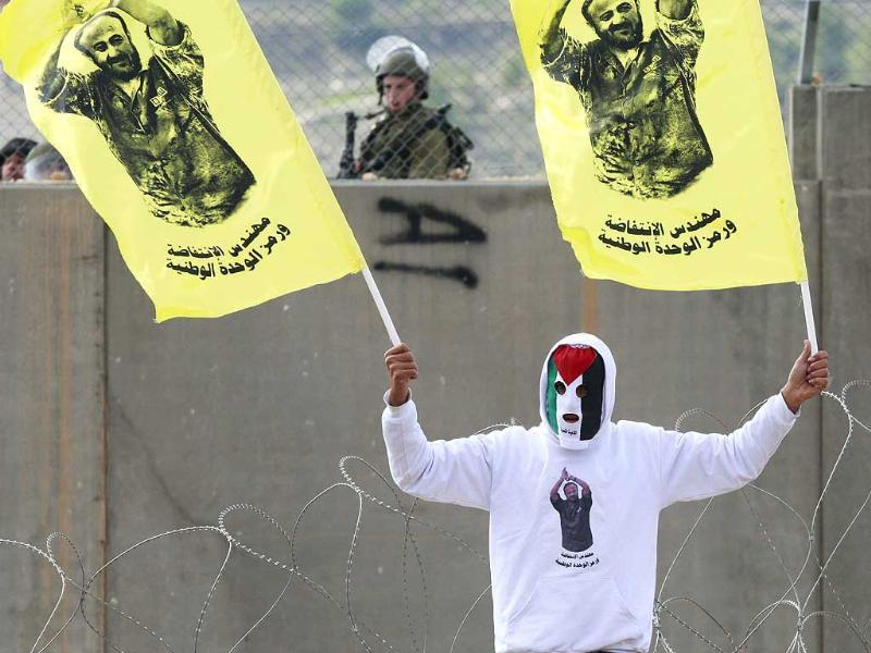 A masked Palestinian holds flags with the image of an imprisoned Palestinian leader Marwan Barghouti during a protest against Israel's separation barrier in the West Bank village of Bilin, near Ramallah. The poster reads: