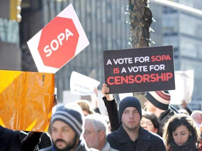 A man holds a sign at a protest by the technology organization New York Tech Meetup against proposed laws to curb Internet piracy outside the offices of US Democratic Senators from New York Chuck Schumer and Kirsten Gillibrand on Third Avenue in New York. Schumer and Gillibrand are co-sponsors of the Senate bill PIPA (Protect Intellectual Property Act). SOPA (Stop Online Piracy Act) is the US House version. AFP PHOTO/Stan Honda