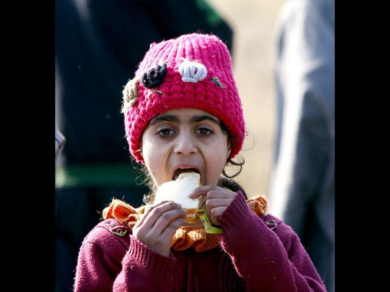 A stranded girl eats bread toast at Jammu before being airlifted by special IAF plane to Srinagar on Saturday. The passangers were stranded for the last ten days. HT Photo/Nitin Kanotra.