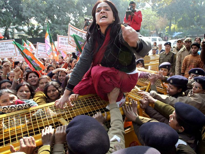One of the BJP women wing members climbs a police barricade as they protest against Congress general secretary Rahul Gandhi's remarks against party leader Uma Bharti, outside AICC headquarters in New Delhi. PTI Photo