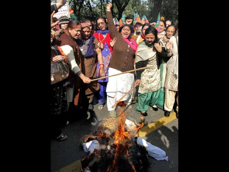 BJP women wing members raise slogans as they burn an effigy of Congress general secretary Rahul Gandhi during a protest over his remarks against party leader Uma Bharti, outside AICC headquarters in New Delhi. PTI Photo/Kamal Kishore