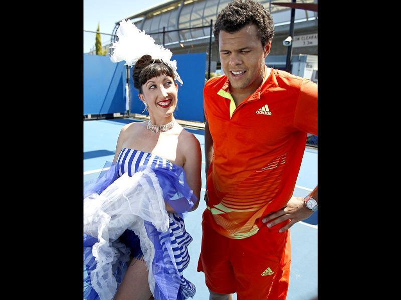 Jo-Wilfried Tsonga of France, right, poses with a cancan dancer at the Australian Open tennis championship in Melbourne, Australia. (AP Photo/Shuji Kajiyama)