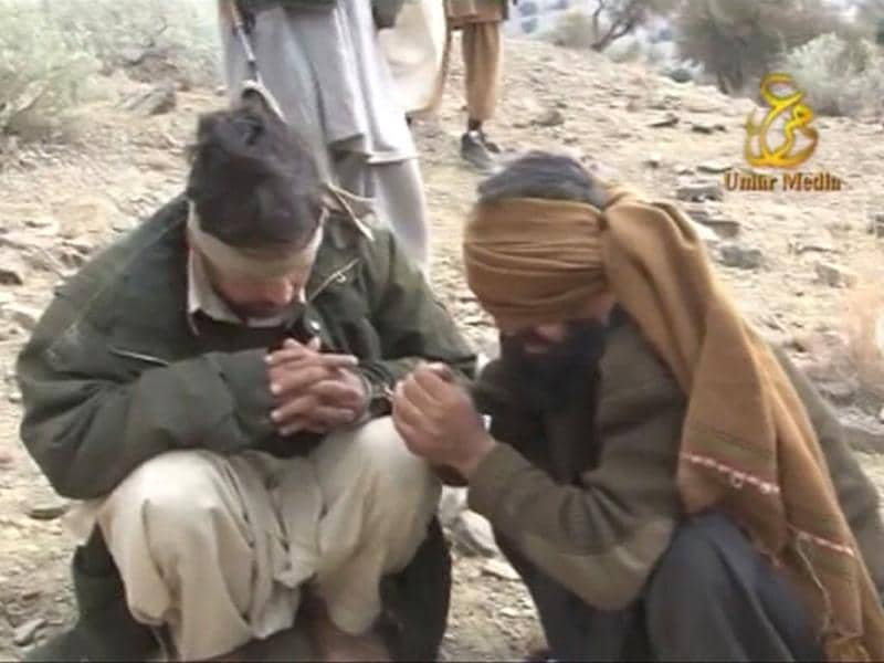 Blindfolded Pakistani soldiers sit on the ground in this still image taken from a video obtained by Reuters. Fifteen Pakistani soldiers stood blindfolded, handcuffed to each other on a barren hilltop as one of their bearded Taliban captors held an AK-47 rifle and spoke with fury about revenge.