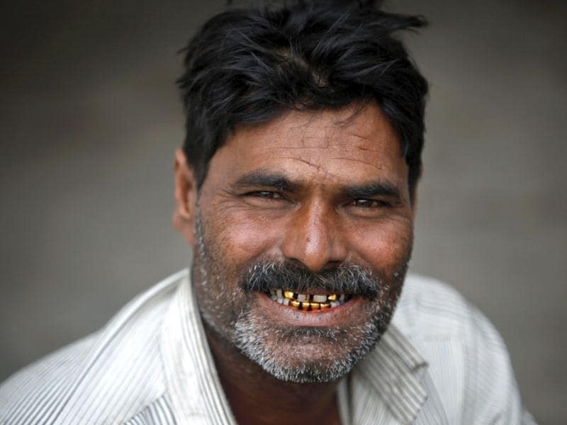 Welljee, 40, a fisherman from India smiles to show his gold ornament-decorated teeth while sitting with others in a police station in Karachi after being detained in Pakistan waters. (Reuters)