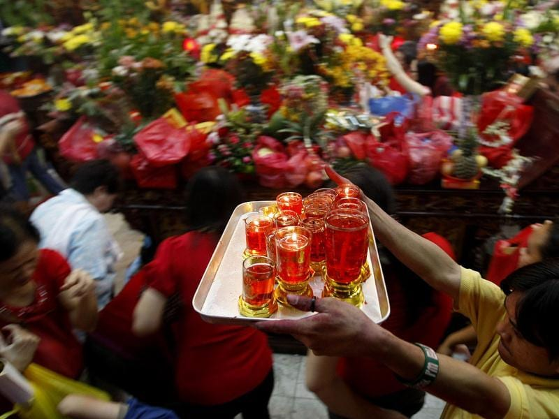 A man carries a tray of candles as others pray inside a Chinese temple in celebration of the Chinese New Year at Manila's Chinatown district in the Philippines. This year is the Year of the Dragon in the Chinese calendar. AP Photo/Bullit Marquez