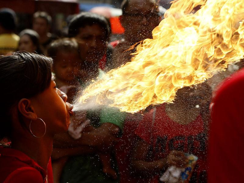 A performer breaths fire during a dragon dance performance in celebration of the Chinese New Year at Manila's Chinatown district in the Philippines. This year is the Year of the Dragon in the Chinese calendar. AP Photo/Bullit Marquez