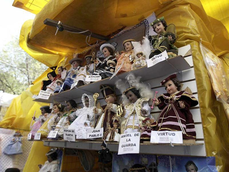 Dolls representing baby Jesus, dressed in traditional Mexican clothing, are displayed by a street vendor for the