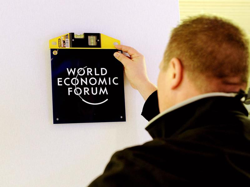 A worker puts World Economic Forum (WEF) logos on the wall of the congress center in the Swiss resort of Davos. (AFP Photo/Vincenzo Pinto)