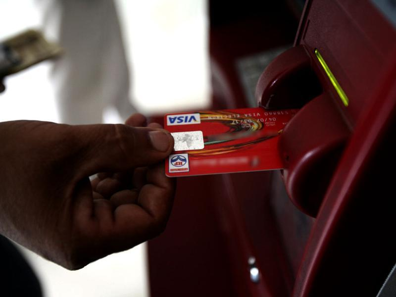 DIP AND DUPE: A customer uses his card to withdraw money from an ATM. (Reuters)
