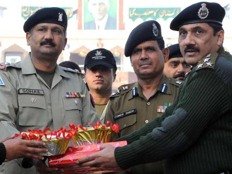 Border Security Force (BSF) Deputy Inspector General (DIG) Sanjeev Bhanot (R) poses with Pakistani Rangers Wing Commander Sohail (L) as they exchange gifts during a ceremony to celebrate India's 63th Republic Day at the India-Pakistan Wagah border. AFP Photo/Narinder Nanu