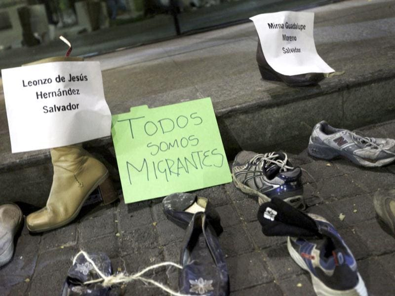 Shoes are seen next to placards during an event organized by Amnesty International to kickstart their campaign urging the public to donate socks to migrants, outside the Registration and Personnel identification building in Mexico city. The placard in center reads,