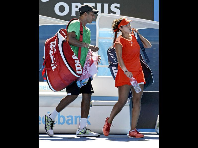 Sania Mirza and Mahesh Bhupathi leave Rod Laver Arena after they lost to Bethanie Mattek-Sands of the US and Horia Tecau of Romania in the mixed doubles semifnal at the Australian Open tennis championship, in Melbourne. AP Photo/Sarah Ivey