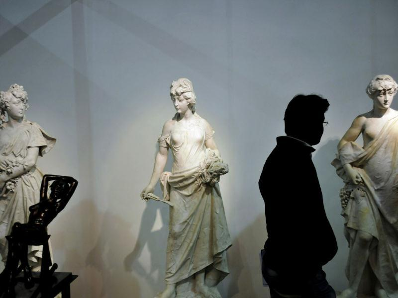 A visitor looks at sculptures by Carlo Nicoli called