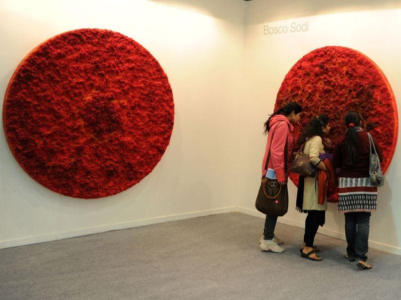 Visitors look at a works of art by Bosco Sodi at the India Art Fair in New Delhi. AFP Photo/Sajjad Hussain