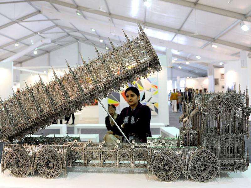 A visitor looks towards Dump truck 2010 made by Wim Delvoye at the India Art Fair in New Delhi. AFP Photo/Sajjad Hussain