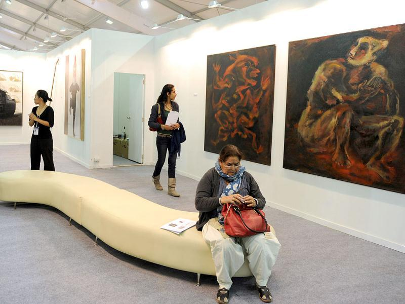 Visitors look at paintings by Paritosh Sen at the India Art Fair in New Delhi. AFP Photo/Sajjad Hussain