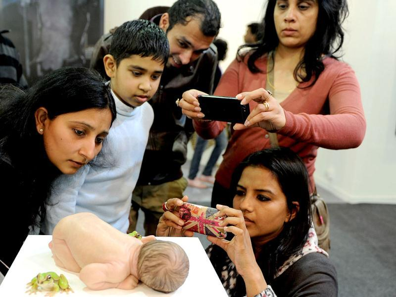 Visitors take pictures of an artwork representing a newborn child by Australian artist Sam Jinks at the India Art Fair in New Delhi. AFP Photo/Sajjad Hussain
