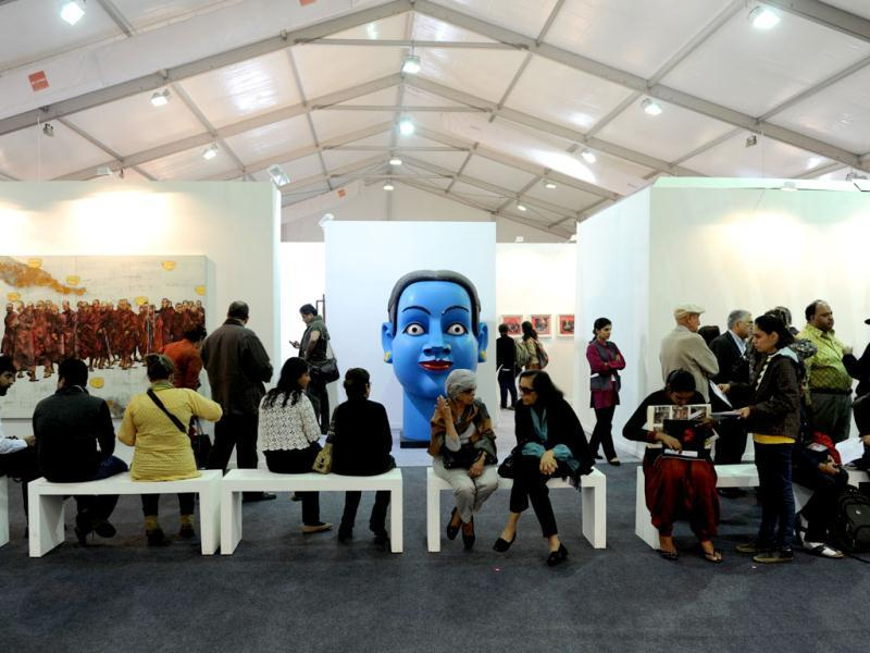 Visitors look at a works of art at the India Art Fair in New Delhi. AFP Photo/Sajjad Hussain