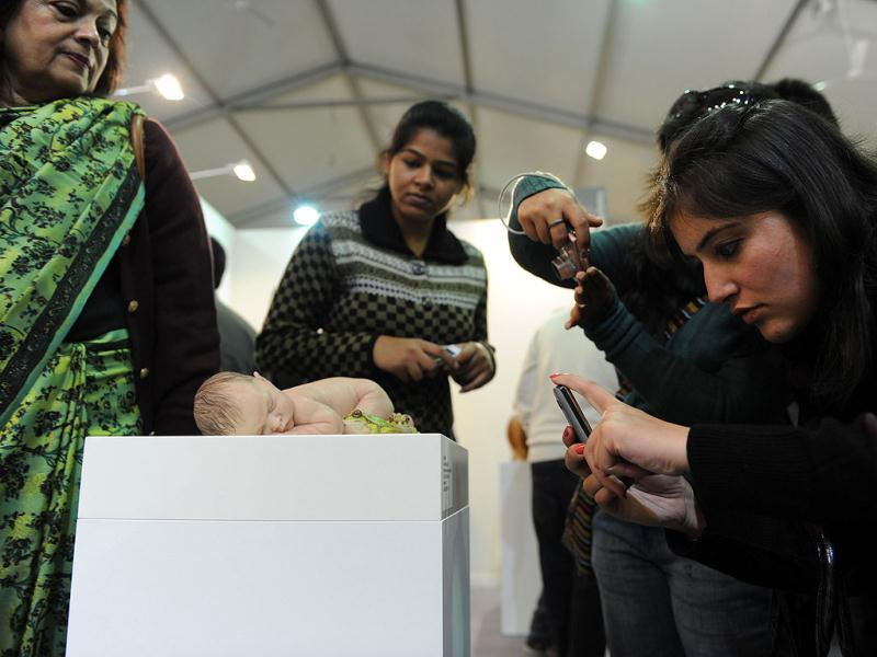 Visitors take pictures of an artwork representing a newborn by Australian artist Sam Jinks at the India Art Fair in New Delhi. AFP Photo/Sajjad Hussain