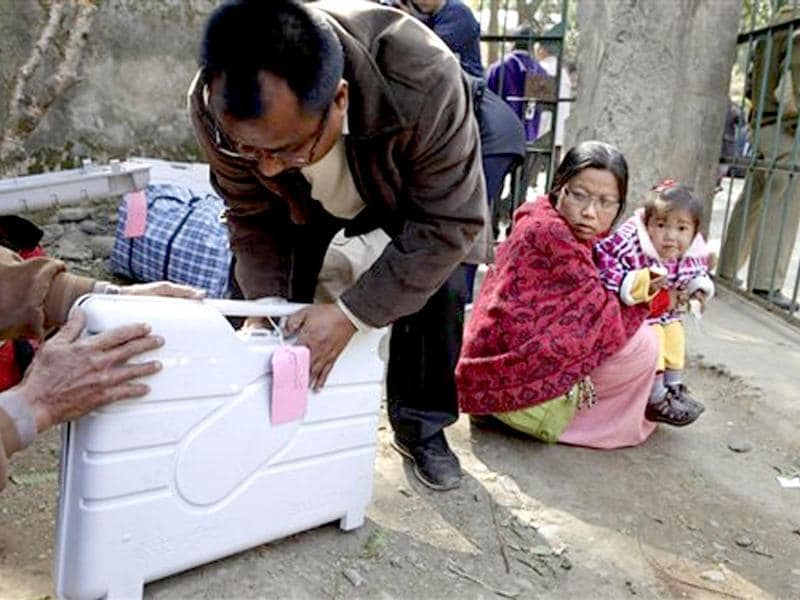 A polling officer closes an electronic voting machine after checking as his wife and child wait before they leave for a polling station on the eve of the state assembly election in Bishnupur district of Manipur. AP/Anupam Nath